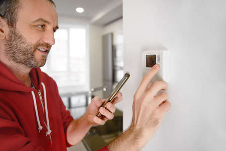 Joyful man looking at his smartphone how the temperature of the heater in a smart home is regulated.
