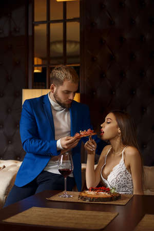 restaurant and holiday concept - Luxurious couple eating at restaurant.The girl eats from the hands of a guy bruschetta.