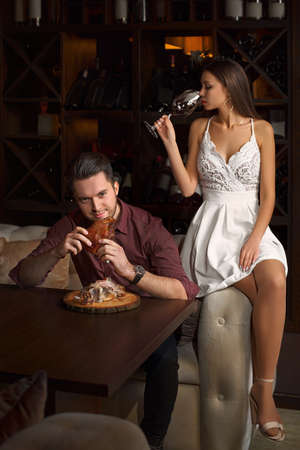 The guy eagerly eats a pork knuckle. Lady sitting on a couch, with a glass of red wine, on a dark background in a restaurant. Banque d'images