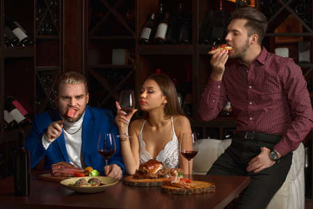 two Guys eagerly eat food in a restaurant, and a girl with a glass of red wine misses, on a dark background in a restaurant.