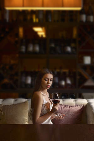Elegant young woman sitting in restaurant and having good time alone. Lady drinking glass of wine, on dark background. Banque d'images
