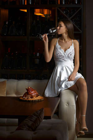 Elegant young woman sitting in a restaurant and have a good time alone. Lady drinking a glass of wine, on the table pork shank against a dark background.