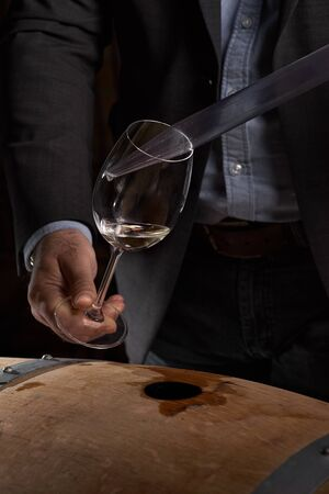Sommelier makes a selection of red wine from an oak barrel. ecological wine production on the farm. close up, low key