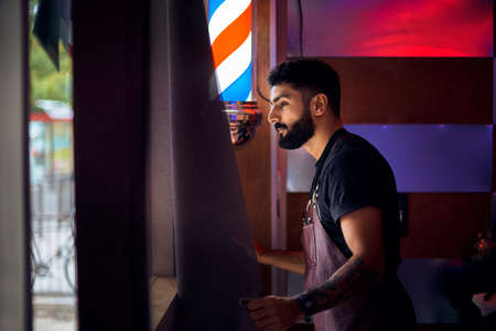 Young hairdresser at his hairdresser. a man with a beard is standing by the window and looking at the street.