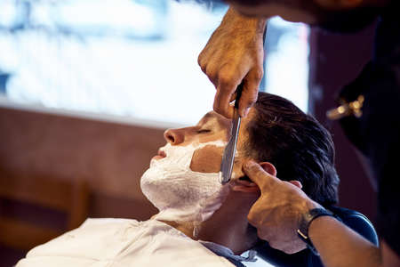 Shaving process of beards in Barbershop. Master makes the client shave his beard with vintage straight razor. Work in the Barber shop, The process of the hairdresser.