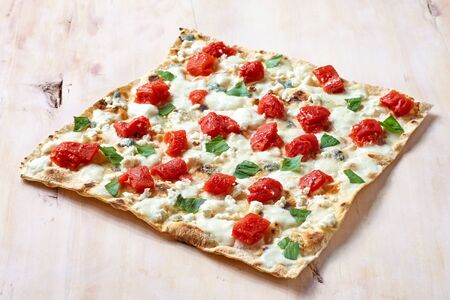 Traditional Tarte Flambee with Creme Fraiche,tomato and cheese on a wooden cutting board, traditional Alsatian pie, rustic style, top view. Standard-Bild