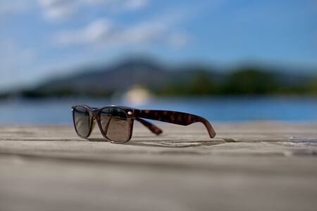 Sunglasses closeup on the table on beach towards sunset over sea and coast pier. Holiday, vacation and relaxation conceptual photography. Retro or modern sunglasses at seaside or shore. 版權商用圖片