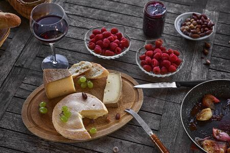Assortment of cheese on a wooden tray with wine, on the table, house terrace, by day, there are no people.