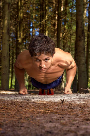 Sportsman with a naked torso and a focused face is ready to push up, in the forest against the background of tree trunks.