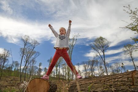 Concept of success, little girl rejoices and reaches out to the sky in the forest. Archivio Fotografico