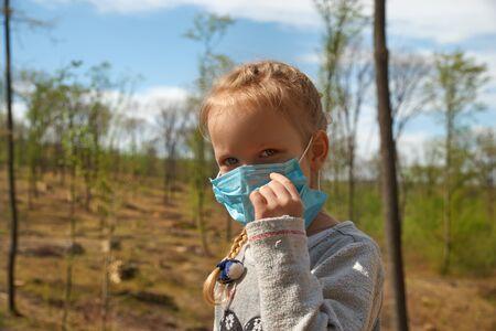 Deforestation. Ecological problems of the planet, quarantine. Little girl in a medical mask at a deforestation site.