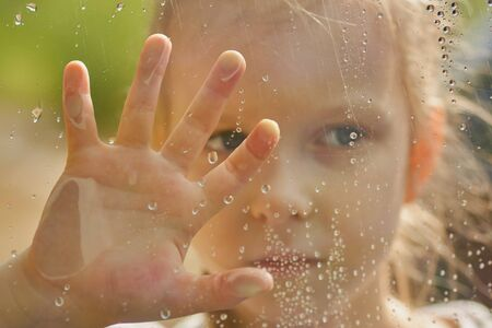 little girl looks out the wet window. Raindrops on the glass. Forest outside the window. Selective focus, Close up. Archivio Fotografico