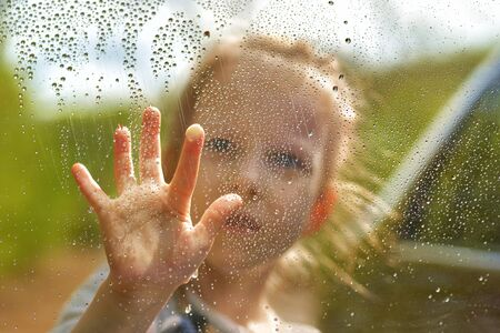little girl blonde draws on a wet window. Raindrops on the glass. Forest outside the window.