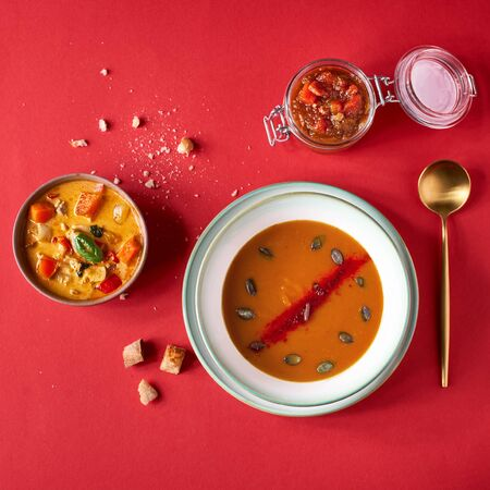 pumpkin soup, Thai curry with pumpkin, pumpkin chutney, delicious vegetable vitamin food menu concept. Top view on red background, selective focus.