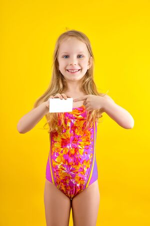 Business card in hand. Smiling girl in a swimsuit, pointing a finger at a white business card on a yellow background. Empty space, mockup. Stock Photo