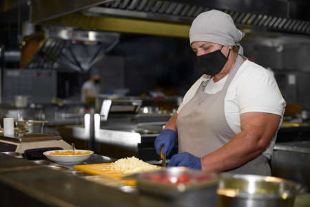cooking, profession and people concept - woman in age chef wearing protective black mask on her face while working in restaurant kitchen