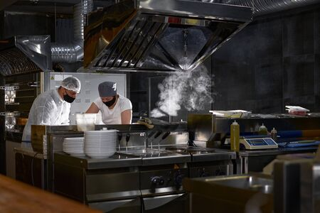 mask on the chefs face in a restaurant: cooks in an open kitchen, a client sees work during a pandemic
