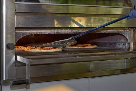 Putting pizza in oven at restaurant kitchen