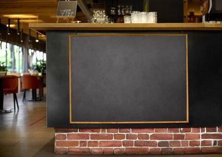 Blackboard menu with easel on wooden table with blur restaurant background, Copy space for adding your content. Mock up Menu