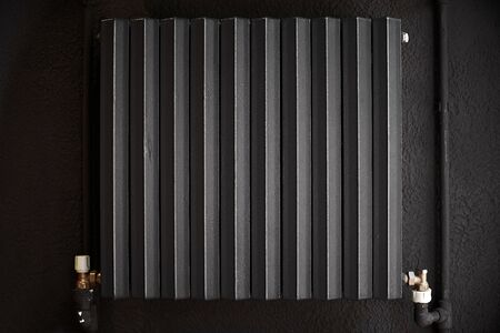 Cast iron radiator heater for home. Black heating battery on the black wall.