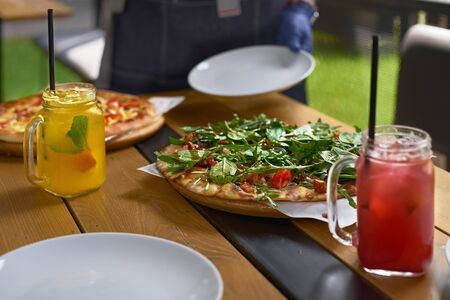 Fresh whole pizza and lemonade on a terrace table in Italy.