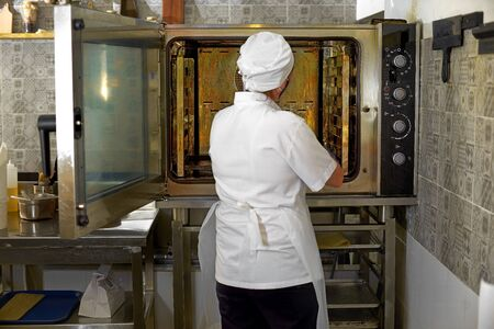 Woman at the open door of a professional oven, metal, glass, shelves, pastries. Cook works in the open kitchen of the restaurant