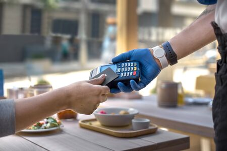 Use payment terminal with contactless credit card with NFC technology for paying in cafe or restaurant, finance concept.