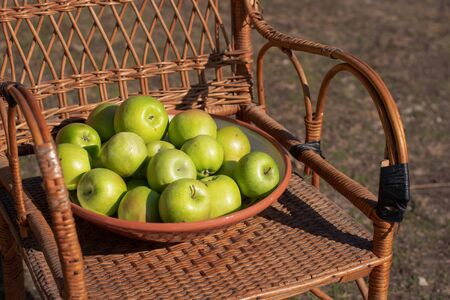 Green apple in a plate on a wicker table. Green grass in the garden. Harvest time. Organic products in a rustic style.