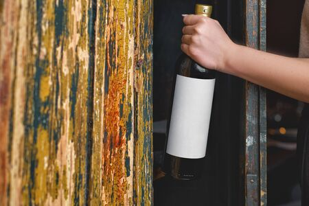 Close up of female hands holding red wine bottle with white blank label against shelf of wine old cabinet in restaurant , mockup. winemakers concept, wine production
