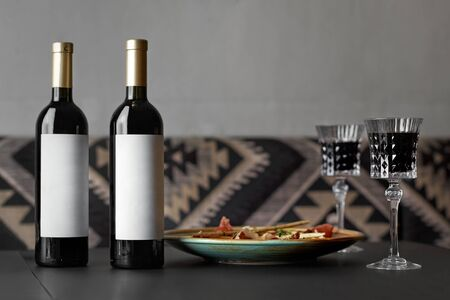 wine tasting on a table in a restaurant. glasses and bottles with empty etiquette for breadboard, appetizer. winemakers concept, wine production. Archivio Fotografico
