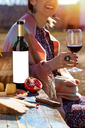 Outdoors table with plate of appetizers and bottle with blank etiquette for mockup. happy girl with a glass of wine in her hands on a sunny day. The concept of emotions.
