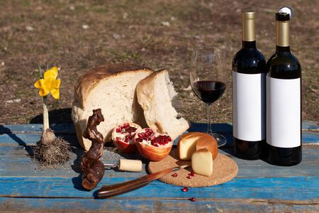 wine tasting outdoors. wine glass and bottle with blank etiquette for mockup, cheese, bread and tomatoes snacks on a haystack. winemakers concept, wine production