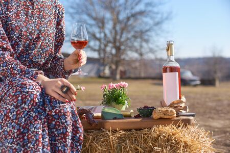 Outdoors table with plate of appetizers and bottle with blank etiquette for mockup. girl with a glass of wine in her hands on a sunny day. The concept of emotions.