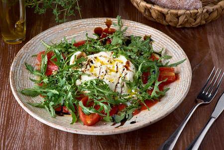Closeup italian buratta salad with pesto and arugula and cherry tomatoes.