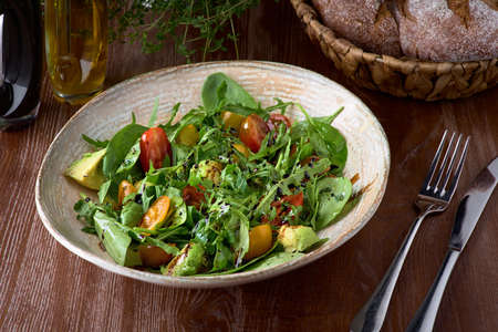 Nutritious low calorie organic vegetable salad made from green leaves and tomato and avocado seasoned with olive oil