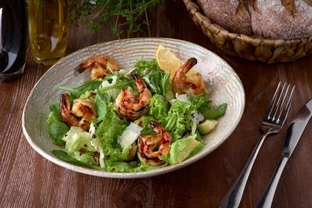 Fresh salad bowl with shrimp, avocado and arugula on wooden background close up. Healthy food. Clean eating. Archivio Fotografico