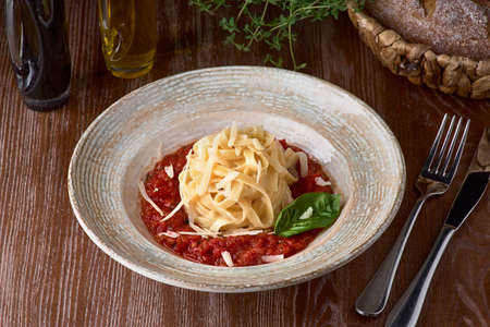 Pasta fettuccine with tomato sauce with the oak Parmesan and basil on a plate, delicious Italian dish.