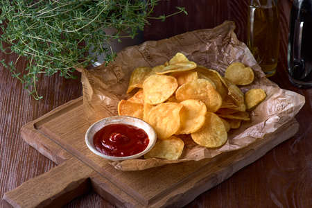 Delicious sweet potato chips with ketchup on a wooden board, beer snack. Concept of unhealthy food.