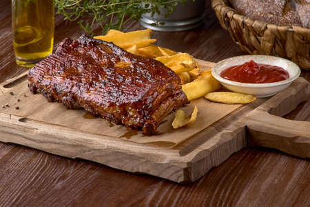 Spicy barbecued pork ribs served with french fries on chopping board. With copy space. Tasty appetizer for beer on a dark background. American food.