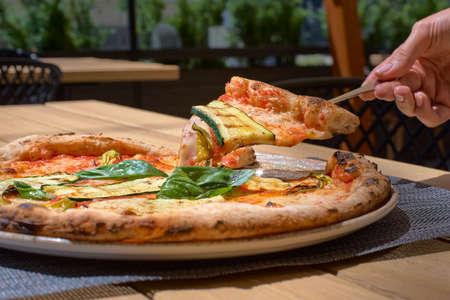 Delicious zucchini flower pizza, Italian Food, Mozzarella, goat cheese, tomato sauce on the terrace closeup Archivio Fotografico