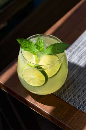 Lemonade or mojito cocktail with lemon and mint, cold refreshing drink or beverage with ice.