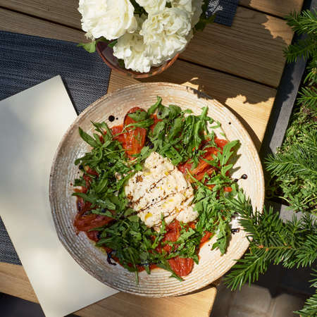 Closeup italian buratta salad with pesto and arugula and cherry tomatoes, on the terrace