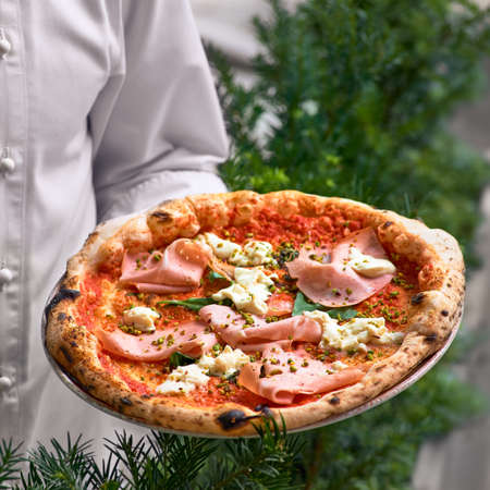 pizza Pinsa Romana in the hands of the chef - traditional recipe of Italian pizza filled with mortadella and cheese on the terrace closeup