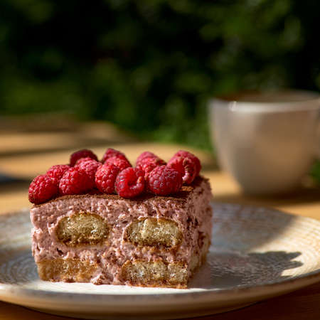 Tiramisu with raspberry on a black plate on a wooden table, morning, dawn. on the terrace closeup