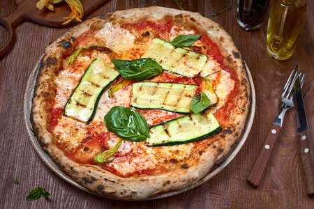 High Angle View Italian Vegan Pizza zucchini on dark a wooden table. Healthy food. 写真素材