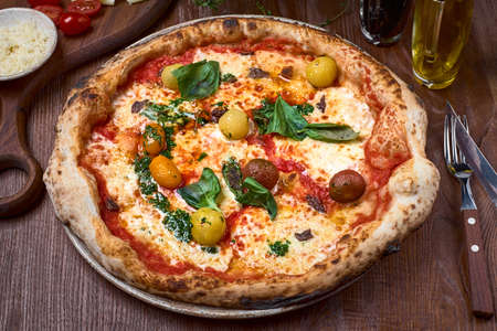 Pizza Napoli, Classic italian pizza with tomato sauce, mozzarella cheese, anchovy and basil on dark a wooden table. Healthy food. 写真素材