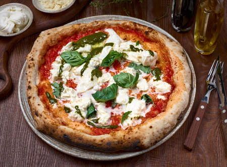 High Angle View of Pizza with tomatoes, basil and stracciatella. rome pizza on dark a wooden table. Healthy food.