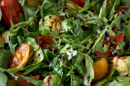 Close-up of organic vegetable salad of green leaves and tomatoes and avocado