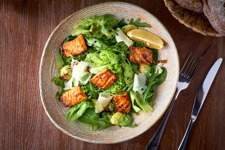 Fresh salad with avocado, arugula and fish fillet, on wooden background close-up. Healthy food. Archivio Fotografico