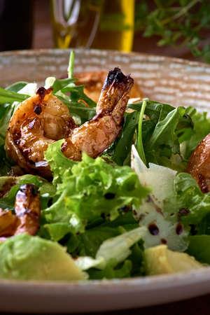 Fresh salad bowl with shrimp, avocado and arugula on wooden background close up. Healthy food. Archivio Fotografico